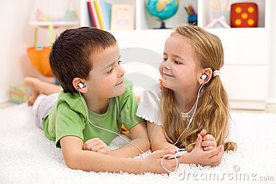 Kids sharing earphones listening to music