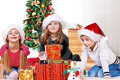 Kids sit beside Christmas presents
