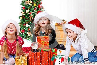 Kids sit beside Christmas presents
