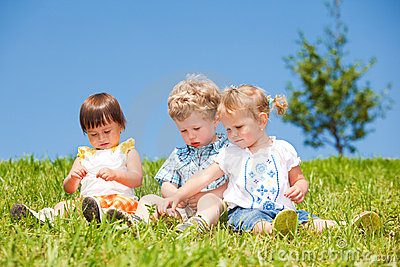 Kids sit on grass
