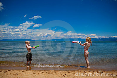 Kids squirting each other with water at the beach