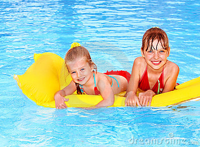 Kids swimming on inflatable beach mattress.