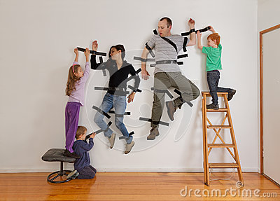 Kids teamwork taping parents to wall