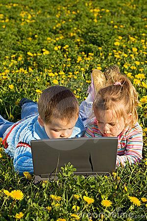 Kids using laptop on the spring flower field