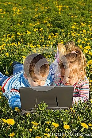 Kids using laptop on the spring flower field