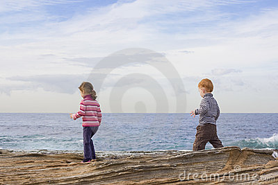 Kids walking on beach rocks