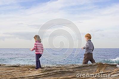 Kids walking on beach rocks