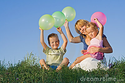 Kids and woman with balloons outdoors