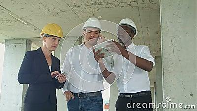 Kierownictwo drużyna przegląda z pastylką na budowie, smartphone, formalni ubierający ludzie czyta budowy pastylkę zbiory