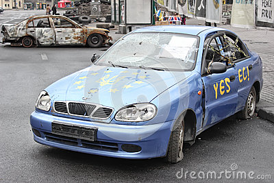 KIEV, UKRAINE - APR 20, 2014: Downtown of Kiev. Broken machine with the EU flag and the coat of arms of Ukraine. Riot in Kiev and Editorial Photography