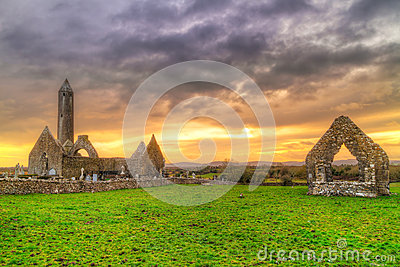 Kilmacduagh monastery with stone tower at sunset