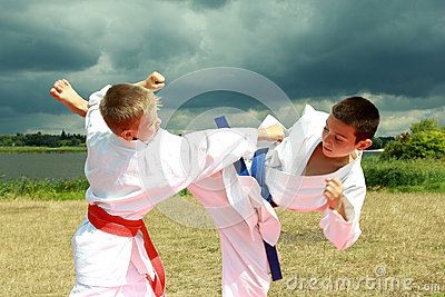 In the kimono two athletes are hitting arm and leg on the background stormy sky