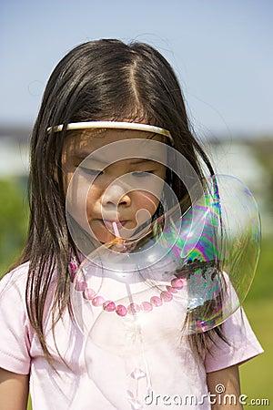 Kind, das eine Luftblase durchbrennt