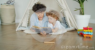 Kind, das Märchen hört, während die Mutter zu Hause in einem gemütlichen Zelt die Geschichte liest stock footage