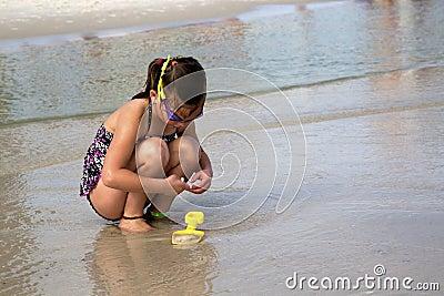 Kind die naar shells bij het strand zoeken.