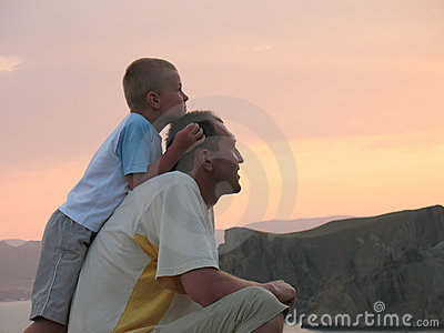 Kind en vader die op zonsondergang kijken