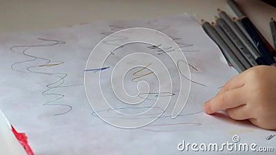 Kind-` s Hände zeichnen mehrfarbige Gekritzel auf einem Blatt stock footage