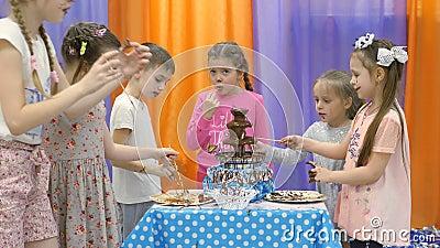 Kind-` s Spielzimmer Kinder essen Schokolade von einem Schokoladenbrunnen stock video footage