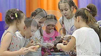 Kind-` s Spielzimmer Kinder essen Schokolade von einem Schokoladenbrunnen stock video