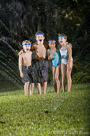 Kinder, die durch Rasensprenger lachen und schreien
