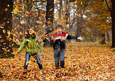 Kinder, die im Herbstpark spielen