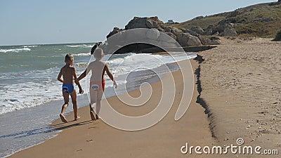 Kinder laufen entlang der Küste Wellen waschen über dem Strand Jungen, die Hände am Strand halten Das Kind im stock video footage