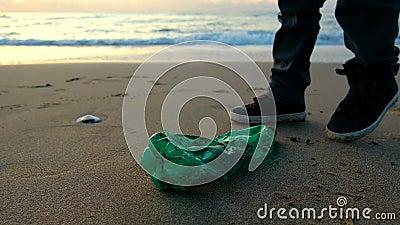 Kinder sammeln Plastikflasche an der Meeresküste, am Sonnenuntergang und an der Wellenbewegung stock video footage