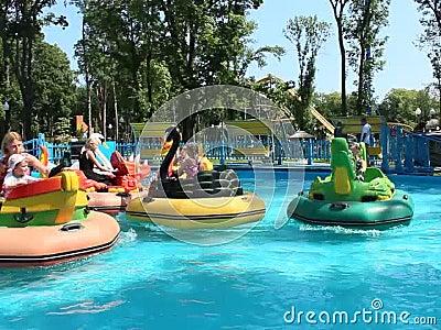Kinder und ihre Eltern reiten die Wasserkatamaran, die in Gorky-Park in Charkiw aufblasbar sind stock video