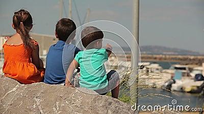 Kinderen kijken naar de baai met jachten stock video