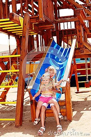 Kinderen op dia in speelplaats. Openlucht park.