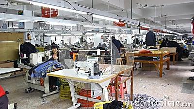 Kinesiska arbetare i en kläderfabrik stock video