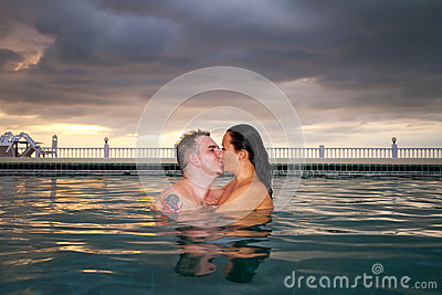 Kiss of loving couple in the swimming pool