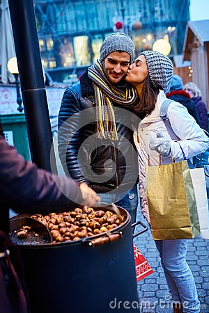 Free Kissing Couple Buying Roasted Chestnuts Royalty Free Stock Image - 100040896