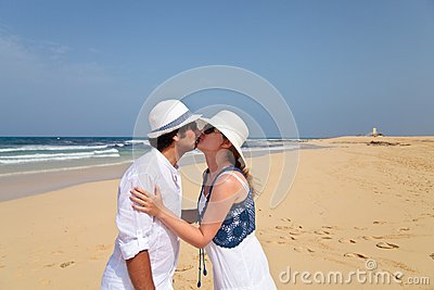 Kissing honeymooners on a beach