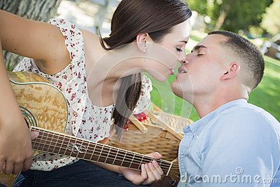 Kissing Mixed Race Couple with Guitar in the Park