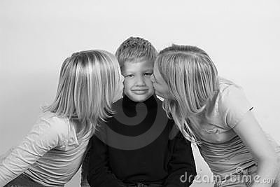 Two girls kissing thier younger brothers cheek.