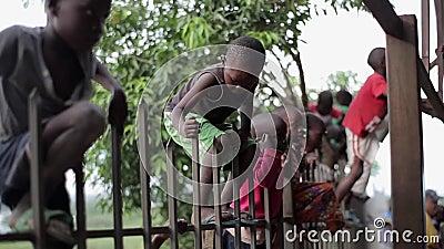 KISUMU, KENIA - 21. MAI 2018: Gruppe Kinder von Afrika-Aufstieg der Zaun Jungen und Mädchen verbringen Zeit draußen zusammen stock footage