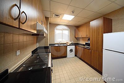 Kitchen with cupboards, washingmachine and fridge