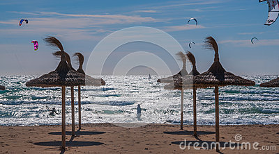 Kite surfers in strong wind, backlight and straw parasols on the beach. Editorial Image