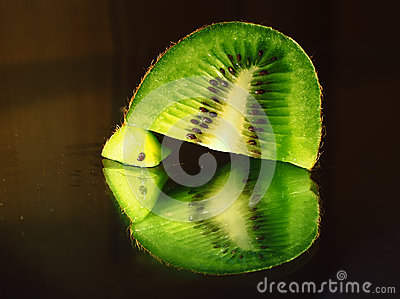 Kiwi fruit in a cut macro piece at mirror Stock Photo