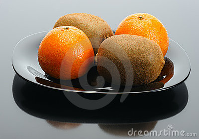 Kiwi and mandarin on a black plate