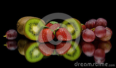 Kiwi, strawberries and grapes on a black background