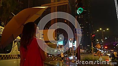 KL, Malaysia Nov 13, 2019:A girl with an umbrella walks near the Petronas Towers. KL, Malaysia Nov 13, 2019: A girl in a red dress and with an umbrella walks stock footage