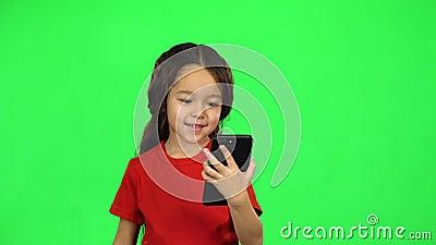 Klein, donkerharig meisje met telefoon stock videobeelden