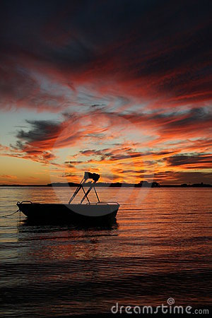 Kleine boot in de waterzonsondergang