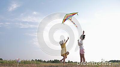 Kleine glückliche Freundinnen spielen mit dem Drachen, schöne Mädchen verbringen aktiv Zeit im Freien mit einem Luftspielzeug im  stock footage