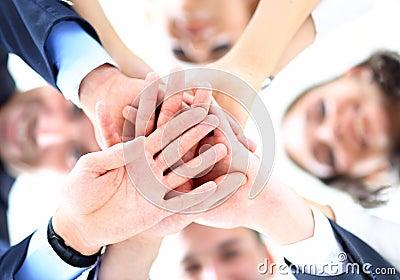 Kleine groep bedrijfsmensen die bij handen aansluiten zich