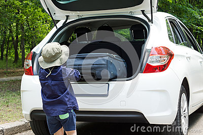 Kleine jongen die zijn koffer laden