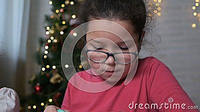 Kleine Kinder schmücken Weihnachtsgebäck mit Sahne auf dem Hintergrund des Weihnachtsbaumes Weihnachten stock video