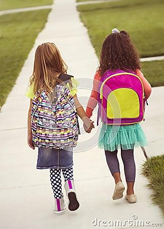 Kleine Mädchen, die zusammen zur Schule gehen